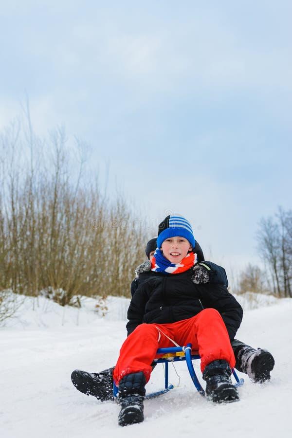 För roliga underhållningar för vinter rider två barn på slädar royaltyfri bild