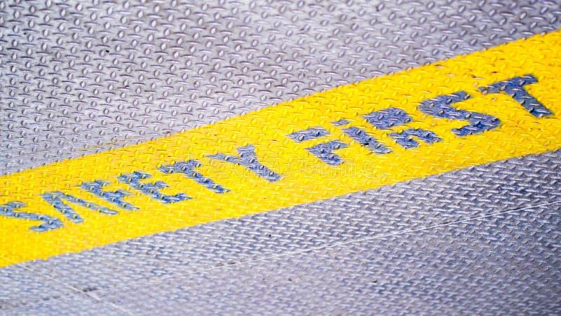 För säkerhet för gulingetikett först symbol för tecken för golv på grå färgmetalltextur arkivfoto