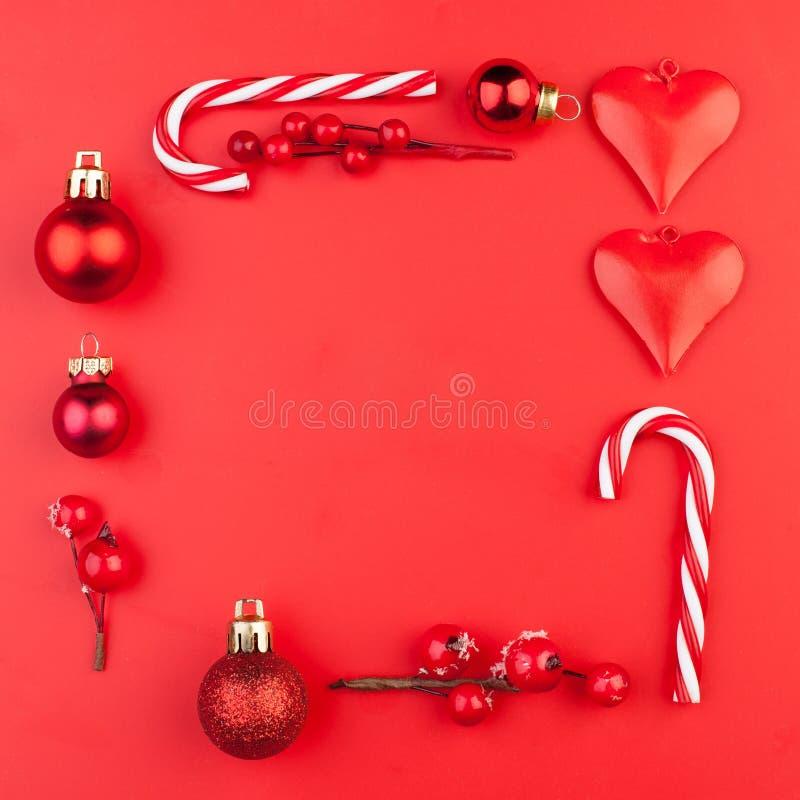 För sammansättningsramen för röd jul gjorde den minsta gränsen av jul godis, struntsaker och järnekbär på röd bakgrund Lekmanna-  arkivfoton
