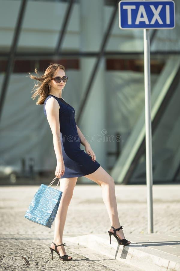 För shoppingpåse för härlig kvinna lyckligt le hållande anseende på stopptaxien royaltyfri bild