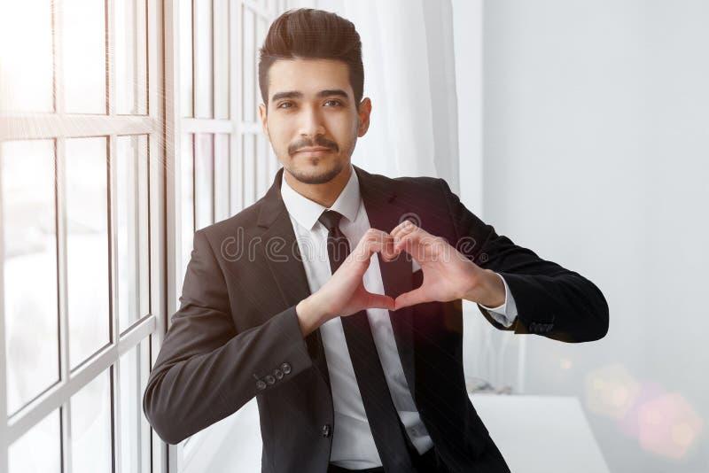 För showhjärta för ung affärsman förälskat tecken royaltyfri foto