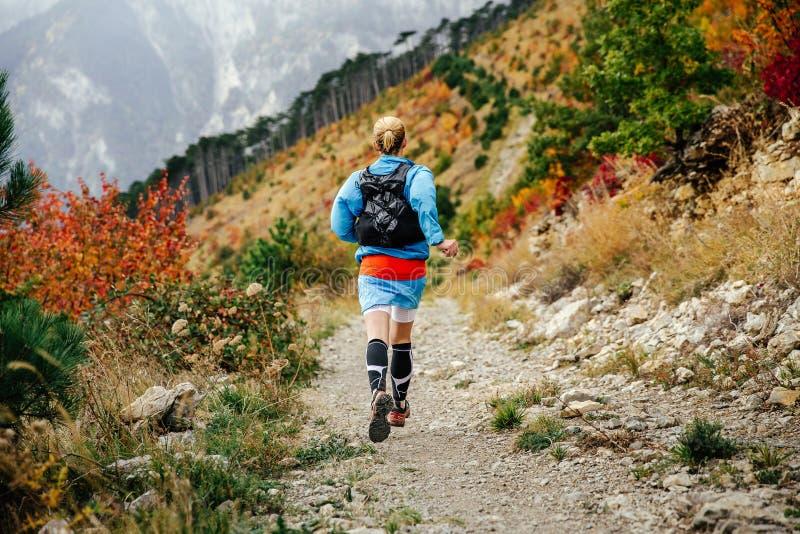 För sikten kör den unga kvinnliga löparen tillbaka bergslingan royaltyfri bild