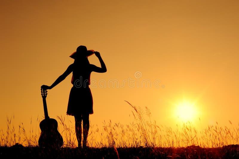 för silhouettesolnedgång för gitarr lycklig kvinna royaltyfri foto