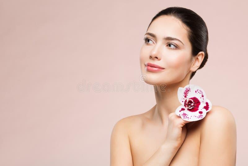För skönhetmakeup för kvinna naturlig stående med blomman på skuldra, härlig flickahudomsorg och behandling fotografering för bildbyråer