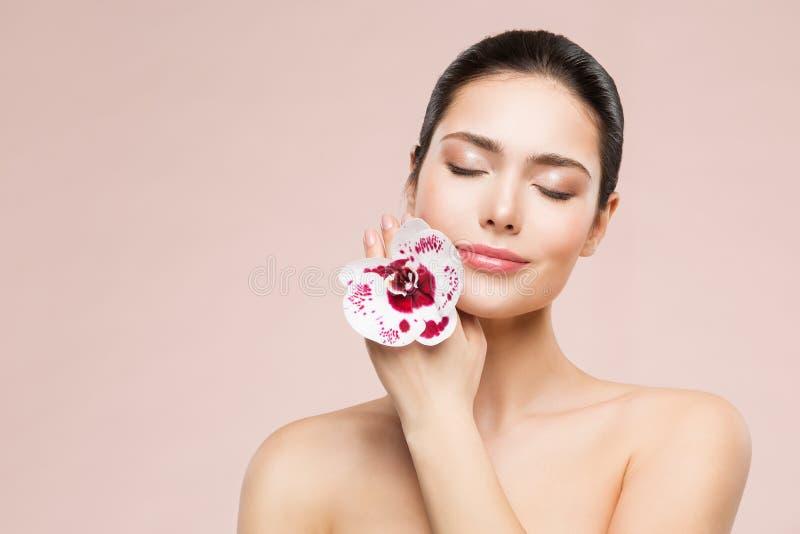 För skönhetmakeup för kvinna naturlig stående och orkidéblomma, lycklig flicka som drömmer hudomsorg och behandling arkivbild