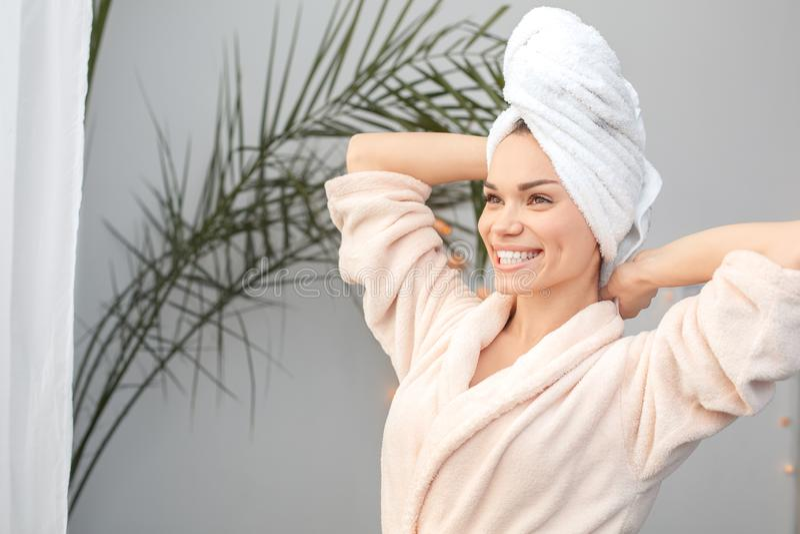För skönhetomsorg för ung kvinna hemmastatt anseende i handduken som sträcker se ut det gladlynta fönstret arkivfoton