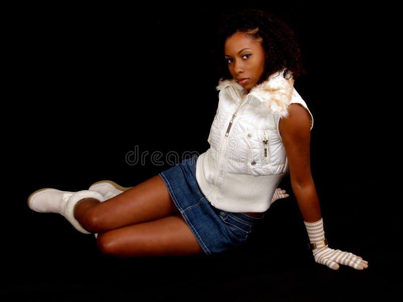 för skirtkvinna för svart jean reclining barn arkivfoto