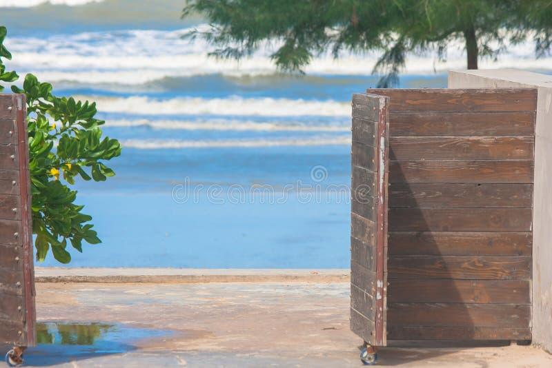 För slut öppen trädörr upp som tar fram stranden royaltyfri foto