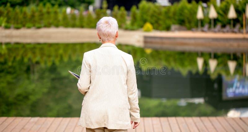 För slut för baksidasikt upp foto av den eleganta kvinnan som strosar på trottoaren arkivfoto