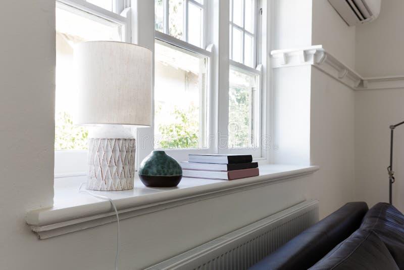 För slut detaljer upp av lampböcker och prydnadobjekt på fönstersi royaltyfri fotografi