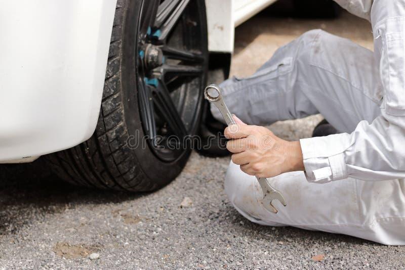 För slut händer upp av den yrkesmässiga mekanikern i den vita enhetliga innehavskiftnyckeln som är klar till att reparera bilen p arkivfoton