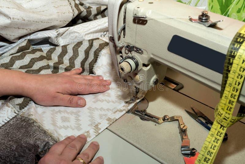 För slut händer upp av sömmerskan som arbetar på symaskinen royaltyfria foton