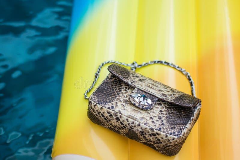 För snakeskinpytonorm för mode lyxig handväska på en uppblåsbar gul madrass i simbassäng Kopiera utrymme arkivfoton