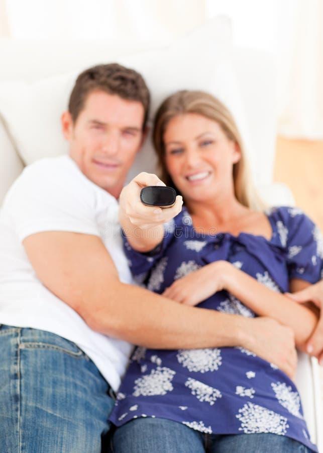 för sofatelevision för vänner liggande le hålla ögonen på royaltyfria foton
