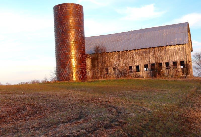 För solnedgång övergiven ladugård och silo royaltyfri foto