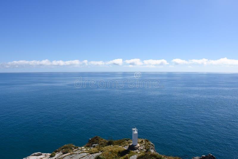 För sommarhav för ensam fyr blå horisont royaltyfri fotografi
