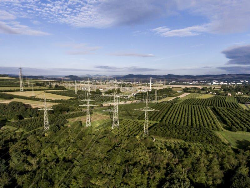 För spänningsmetall för flyg- sikt hög för Hög-spänning för stolpe jordbruksprodukter för frukt för plaantage för träd för landsk royaltyfria bilder