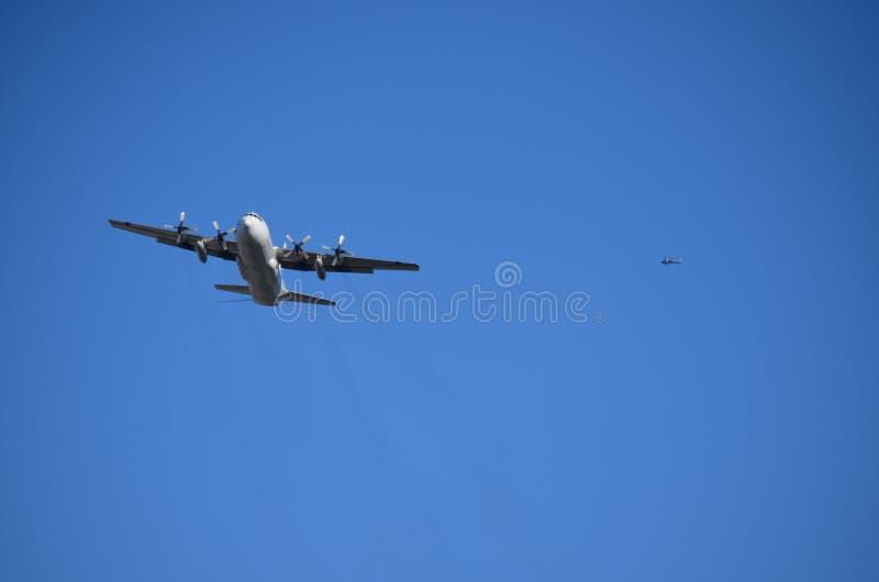 För spiralflygplan för militär fyra flyg med en helikopter på bakgrunden royaltyfria foton