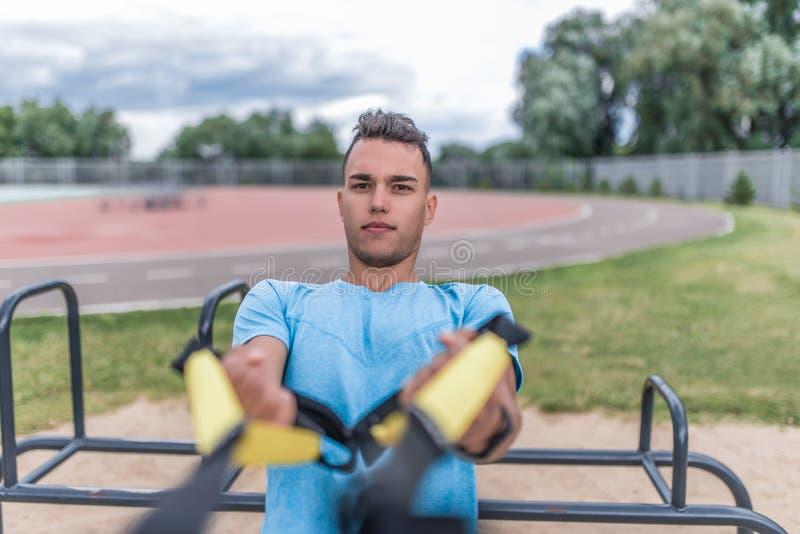 För sportmannen för närbilden vrider om den unga staden för sommar, handtag upp ut på hans gångjärn, remhorisontalstången, sund l arkivfoton