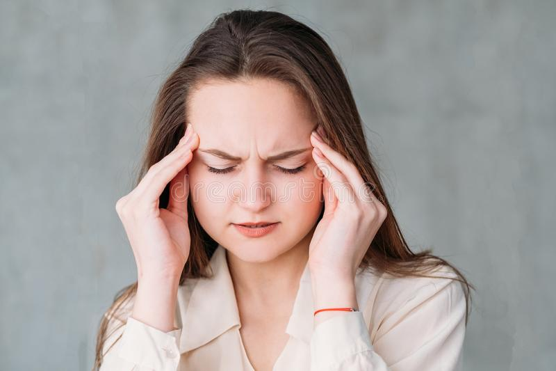För ståendespänning för ung kvinna tempel för handlag för huvudvärk arkivfoto