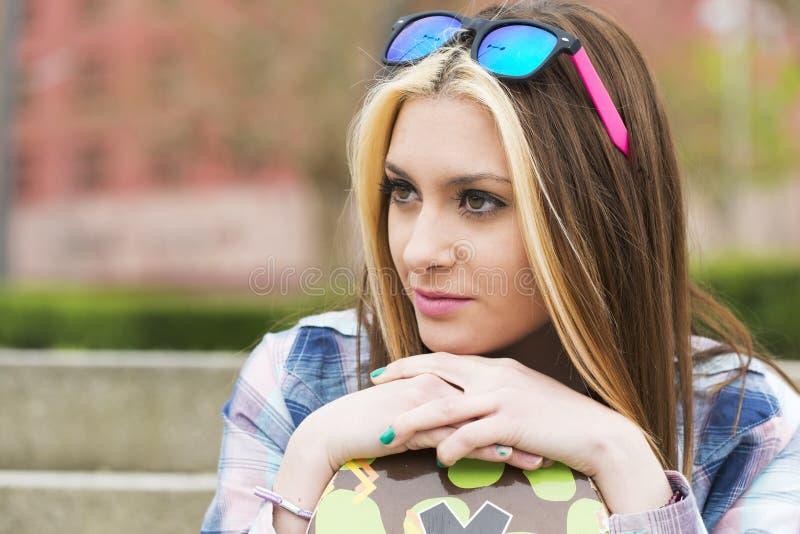 För stads- härlig flicka ståendelycka för Closeup med skateboarden arkivfoto