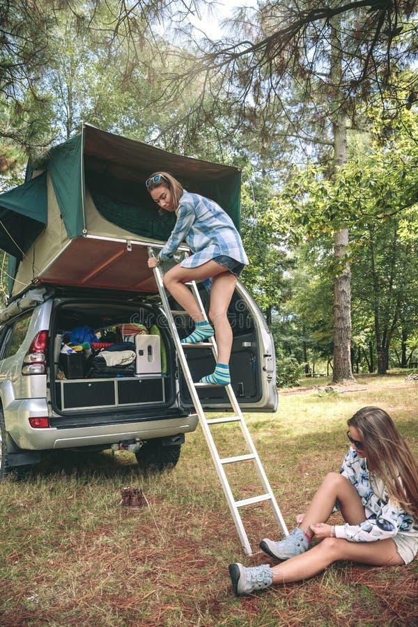 För stegeform för kvinna nedgående tält över bilen royaltyfri fotografi