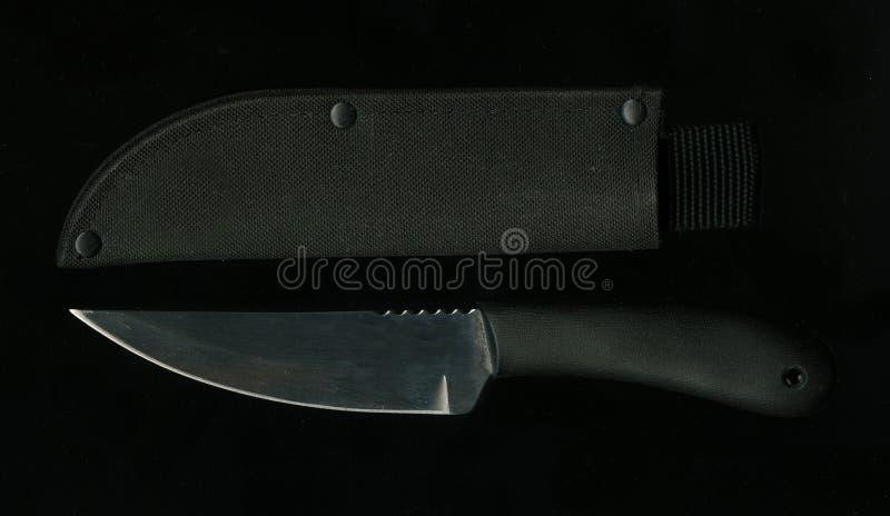 För stiljakt för rostfritt stål avspeglade det militära bladet för kniven och svarta läderskidan som lägger på en svart, yttersid royaltyfria foton