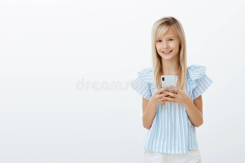 För stolafarsor för liten unge mobiltelefon som spelar lekar Stående av den charmiga lyckliga unga flickan med blont hår, hålland arkivbilder