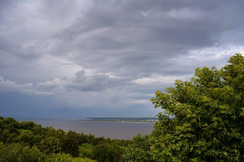 För stormen Åskväderhimmel över skog och floden i molnig dag royaltyfri foto