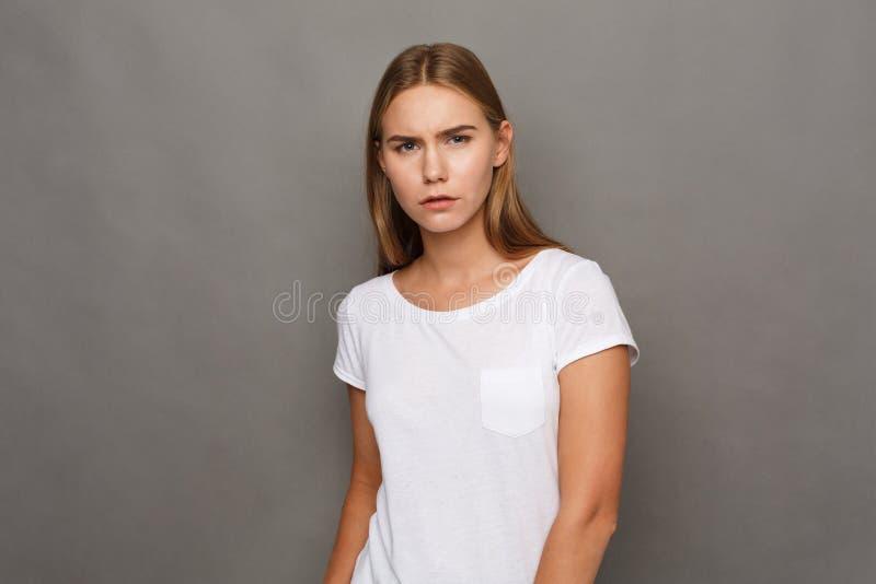 För studioheadshot för ung kvinna stående på grå bakgrund fotografering för bildbyråer