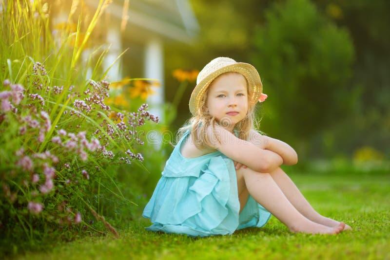 För sugrörhatt för gullig liten flicka bärande sammanträde på gräset på solig sommardag Barn och blommor, sommar, natur och gycke fotografering för bildbyråer