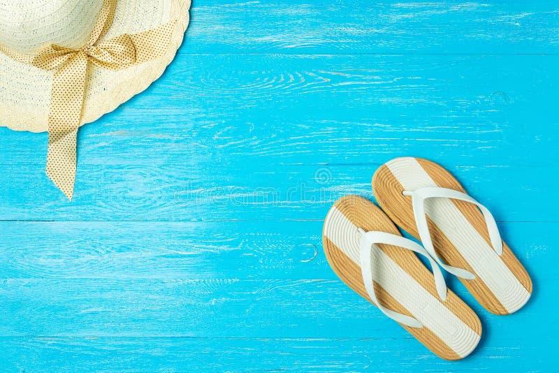 För sugrörhatt för ram eleganta kvinnliga häftklammermatare på blå träbakgrund, copyspace för text, sommarsemester royaltyfri foto