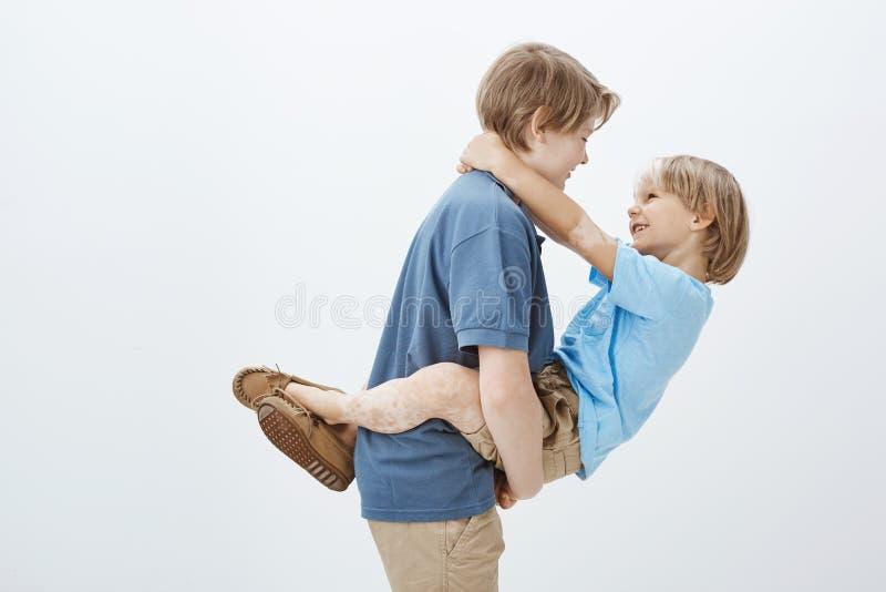 För syskon hjälp alltid Stående av den hållande brodern för bekymmerslös lycklig pojke i armar och att le på honom medan royaltyfria bilder