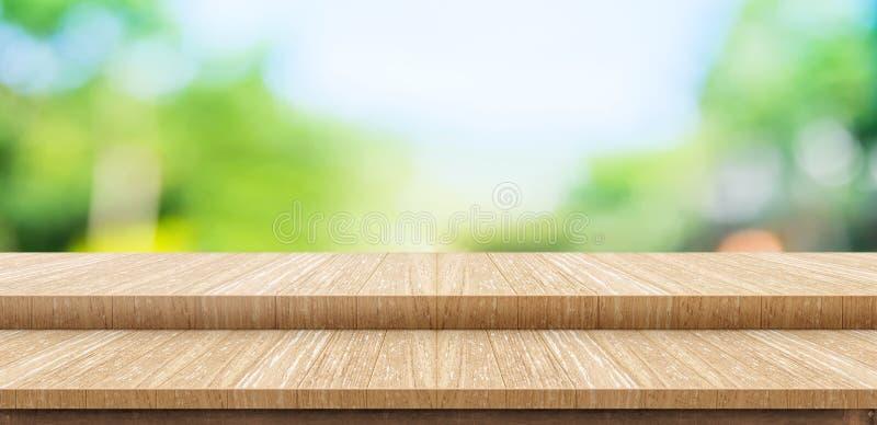 För tabellöverkanten för det tomma momentet parkerar den wood ställningen för mat med suddighetsgräsplan träd b royaltyfria foton