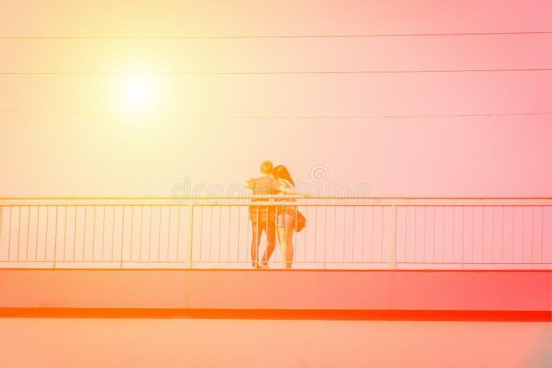 För tagandeselfie för unga par förälskad stående på bron Gult tonat orange royaltyfri bild