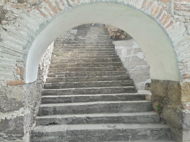 För tegelstentrappuppgång för forntida sten lantlig vit öppning för tunnel för valvgång, gammal lantlig textur, klättringhöjd royaltyfria bilder