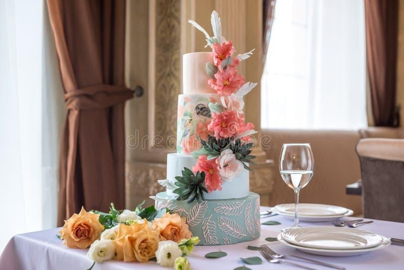 För-tiered kaka för hem- bröllop på tabellen i restaurangen som dekoreras med rosa rosor och gräsplansidor i en lantlig stil arkivbild