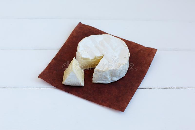 För traditionell läcker mat Normandie för camembertost fransk gourmet- rund mejeriprodukt på lantligt pergament på vit bakgrund arkivbild