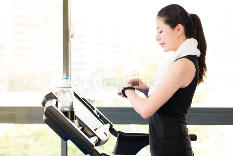 För trampkvarnbruk för asiatisk kvinna rinnande hastighet för puls för kontroll för smartwatch royaltyfri fotografi