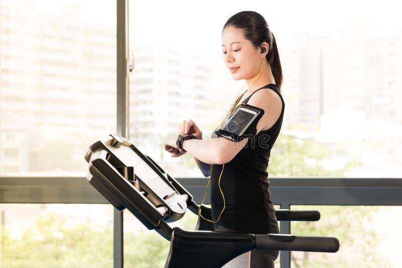 För trampkvarnbruk för härlig asiatisk kvinna som rinnande smartwatch lyssnar royaltyfria bilder