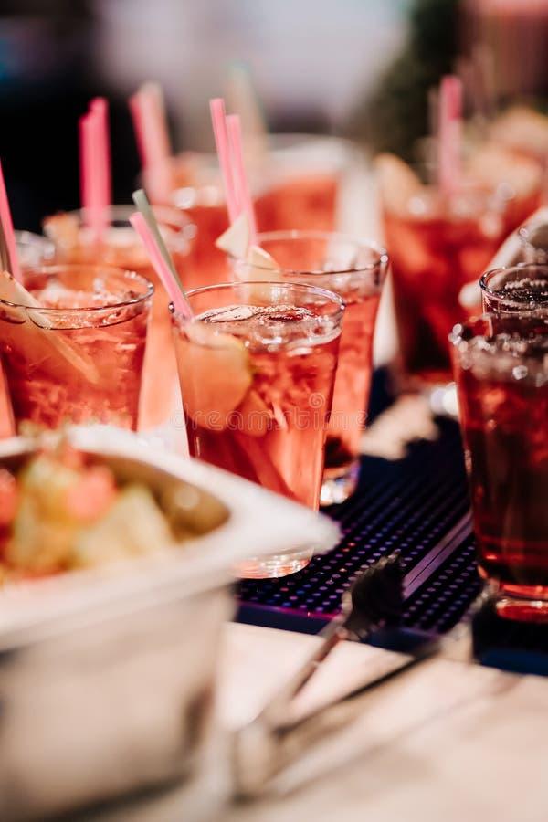 För tranbär- och limefruktsommar för uppfriskning alkoholiserad röd coctail med äppelcider och is arkivfoton
