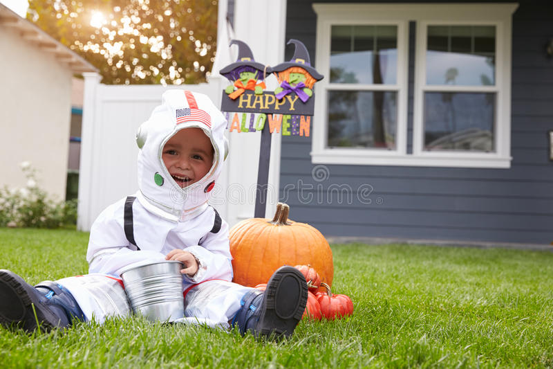 För trick- eller behandlingsastronaut för pojke iklädd dräkt på gräsmatta royaltyfria bilder