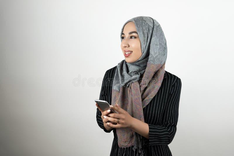 För turbanhijab för ung härlig muslimsk kvinna bärande smartphone för innehav för sjalett i hennes händer isolerade vita bakgrund royaltyfria foton