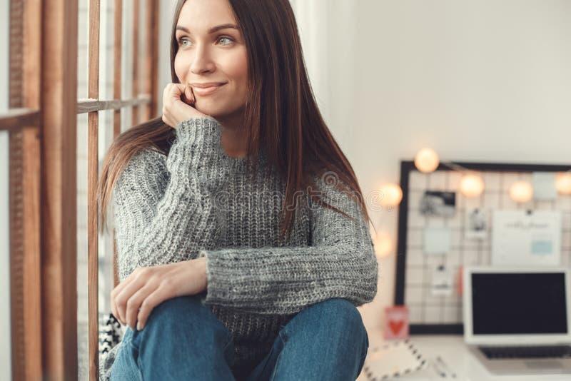 För ung kvinna för freelancer sammanträde för atmosfär för vinter för begrepp för inrikesdepartementet inomhus på fönsterfönsterb arkivfoton