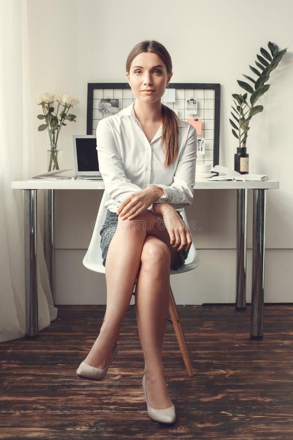 För ung kvinna för freelancer sammanträde för stil för begrepp för inrikesdepartementet inomhus formellt på stol arkivbilder