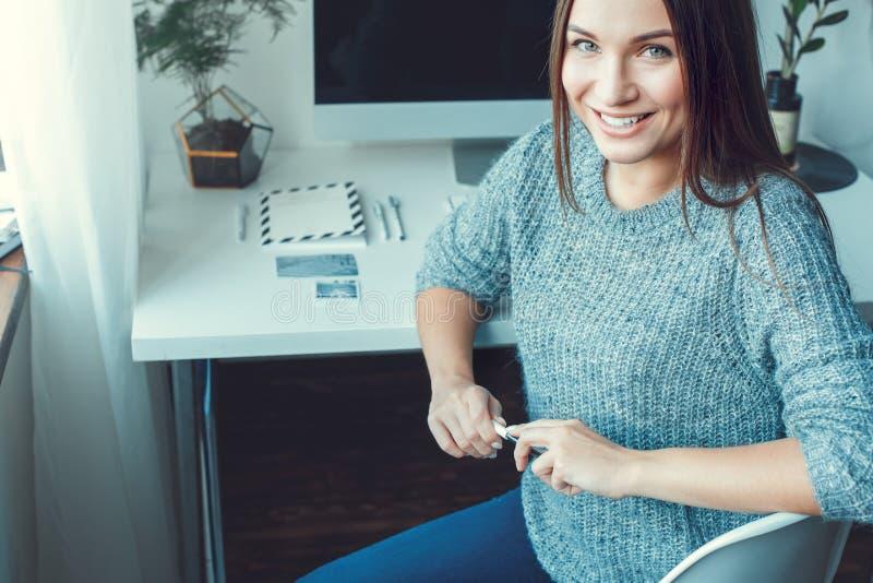 För ung kvinna som för freelancer stil för begrepp för inrikesdepartementet inomhus tillfällig ser kameran royaltyfri fotografi