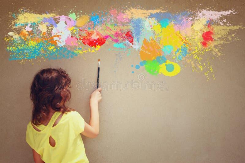 För ungeinnehav för tillbaka sikt gullig borste bredvid texturerade vägg- och målarfärgfärgstänk arkivbild