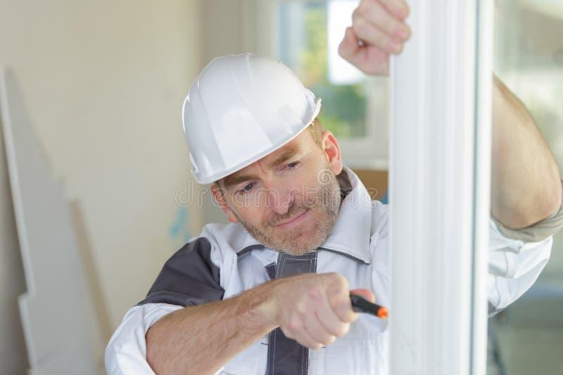 För upvcfönster för arbetare passande ram arkivbild
