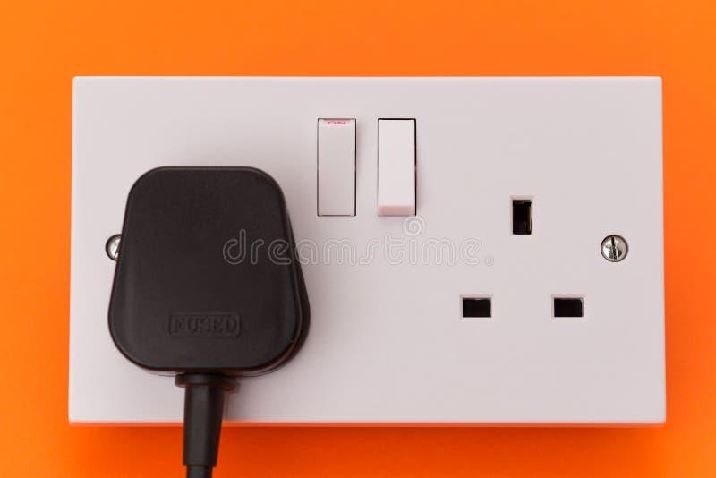 För vägghåligheten för UK pluggar elektriskt uttag och royaltyfri foto