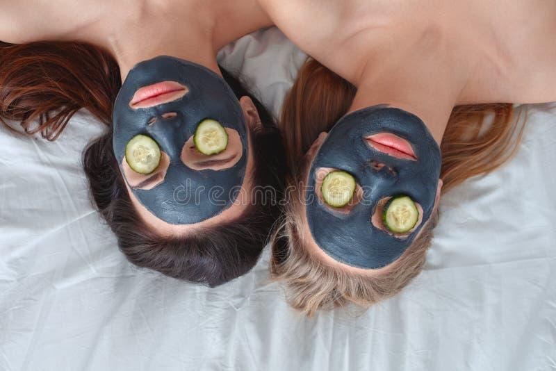 För vänner som hemmastadd skönhetomsorg tillsammans ligger med en maskering på framsida och gurkan på närbild för bästa sikt för  royaltyfria foton
